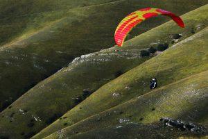 paragleiter fliegt über grüner hügellandschaft der abruzzen